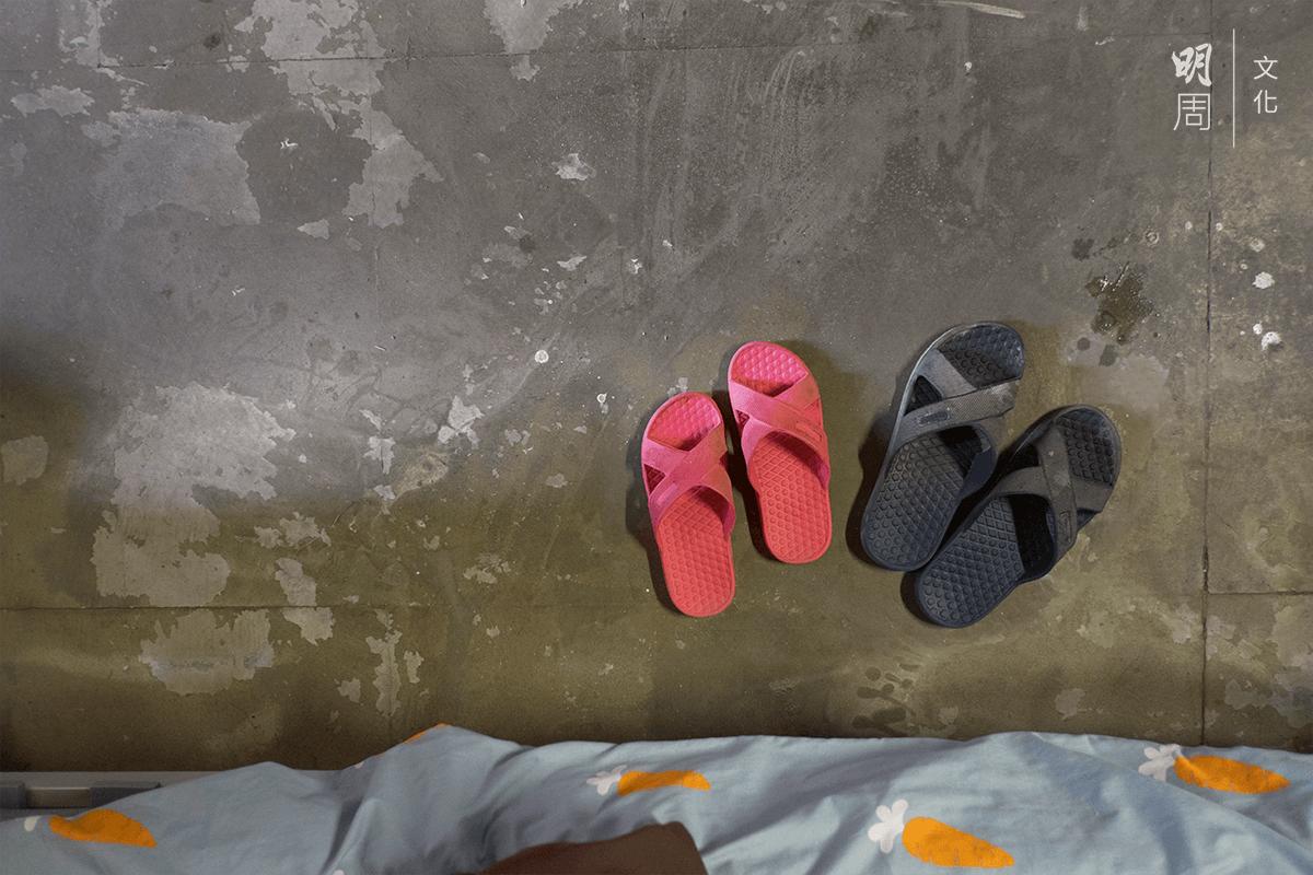 一塊斑駁的地板和兩雙拖鞋