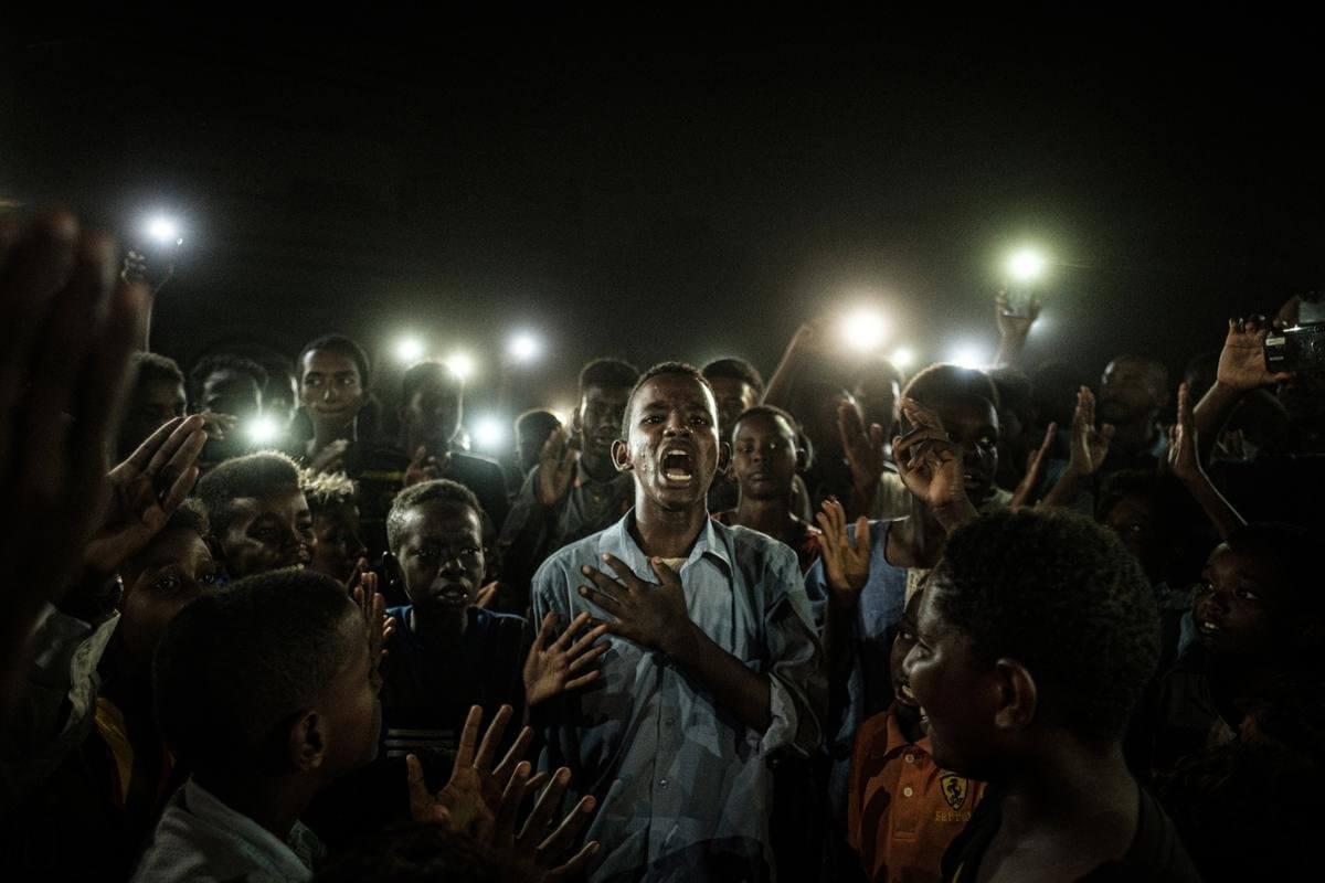 在蘇丹喀土穆一次停電期間,有年輕人在手機燈光下讀詩,示威者高叫口號。(攝影/Yasuyoshi Chiba/法新社)