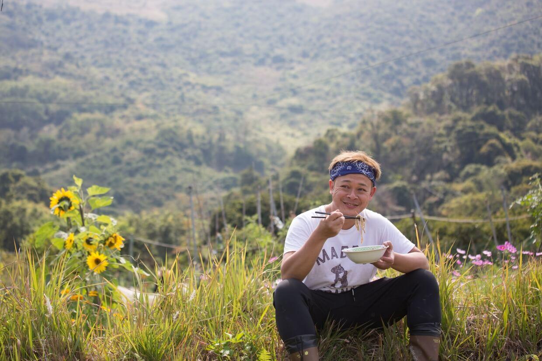 坐在農地旁,梁祖堯一副隨性的坐姿,左手捧大碗,右手握雙筷,仰天望地咀嚼麵條,過了好一會兒,他不禁笑着評價:「都幾crunchy。」