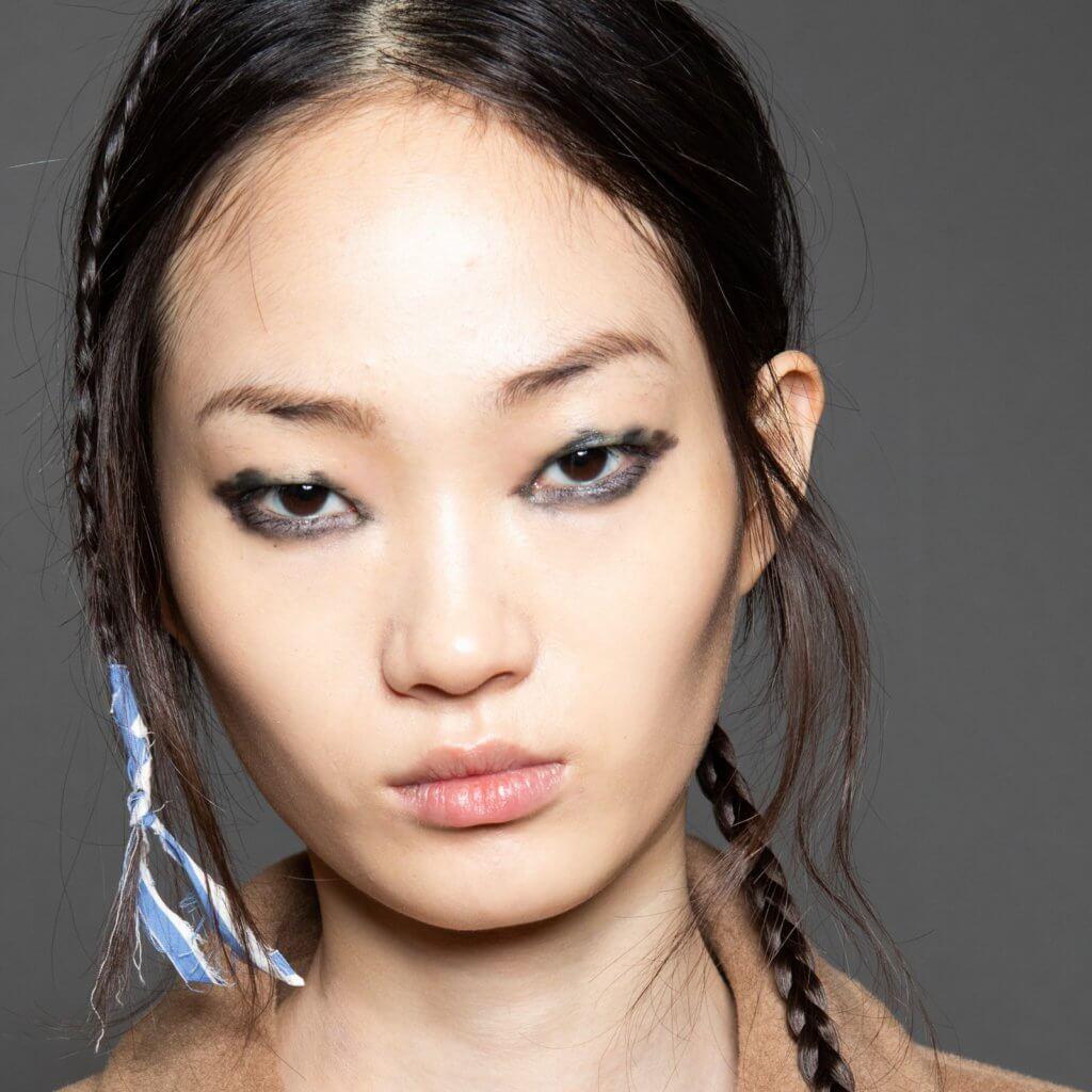 這次用以行騷的妝容給人強悍率性的氣息,海軍藍與墨黑交織,讓暈染式眼線更突出個性,而又不顯「髒」感;髮型方面主要是隨意把頭髮紮起,兩側又各綁上小鬢,完美襯托出是次設計風格。