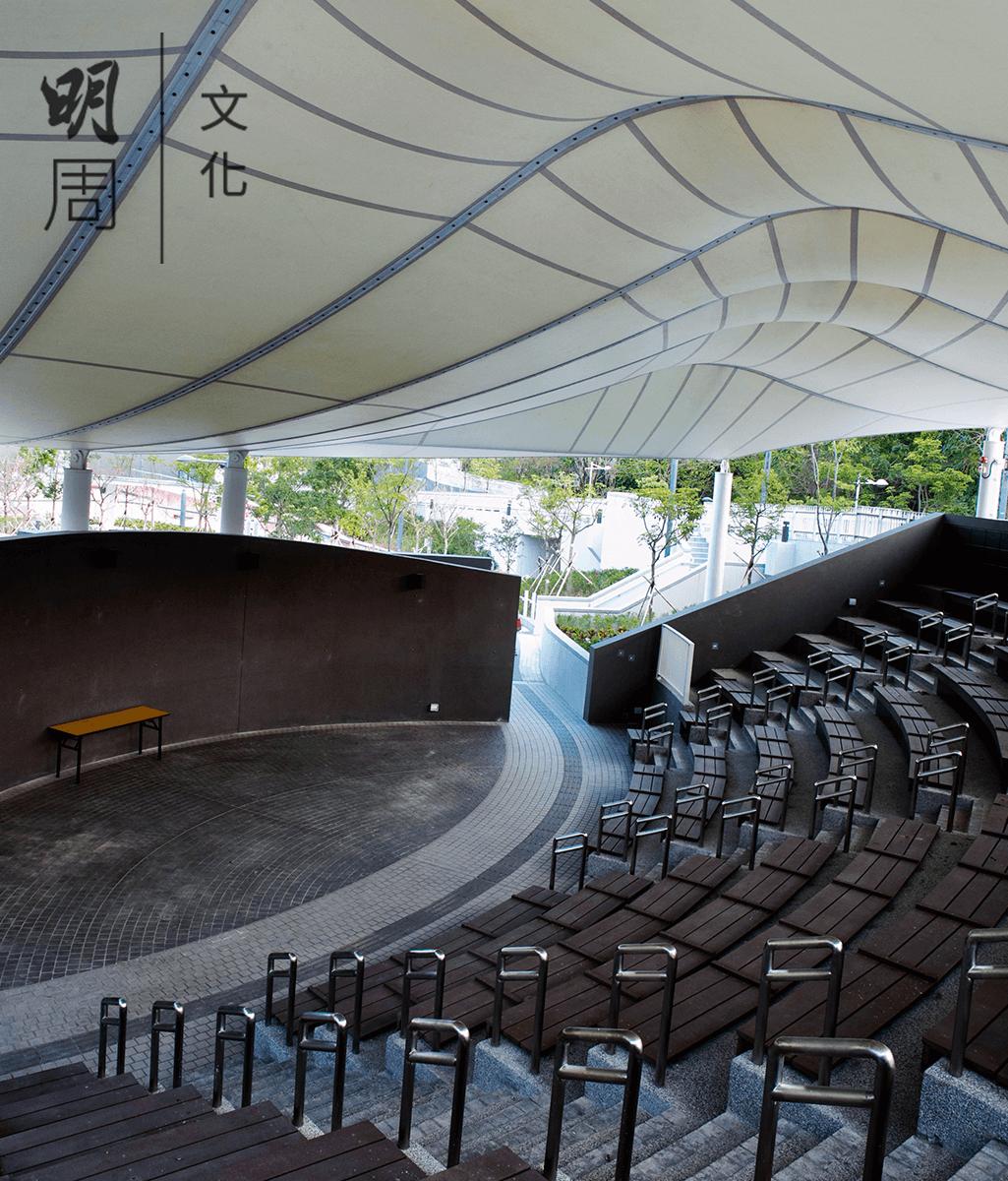 將軍澳市鎮公園的運動場露天劇場, 距離住宅區180米,作為露天表演場地 又不影響居民生活,聲學管理應該怎 樣做呢?天幕可以擋雨又可以隔聲, 表演聲音會從天幕折射到觀眾席,喇 叭都安裝在座位下,座位最末端安裝了吸音板,外面則是石屎隔聲屏障。