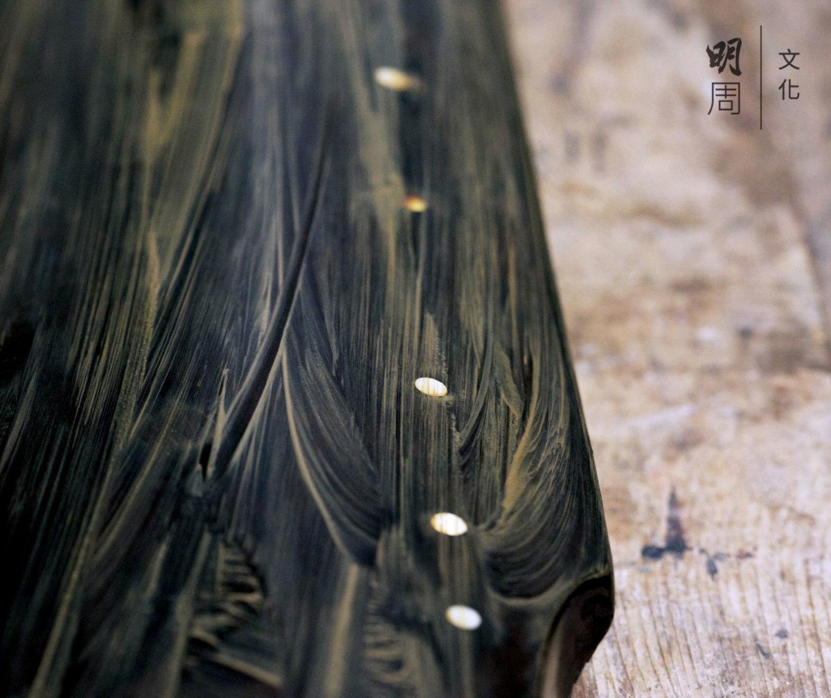 打磨。以幼細水砂紙濕磨至平滑, 再重複髹漆,直至琴身光滑。生漆是琴體表面的保護層,已打磨灰胎的琴坯可髹漆。