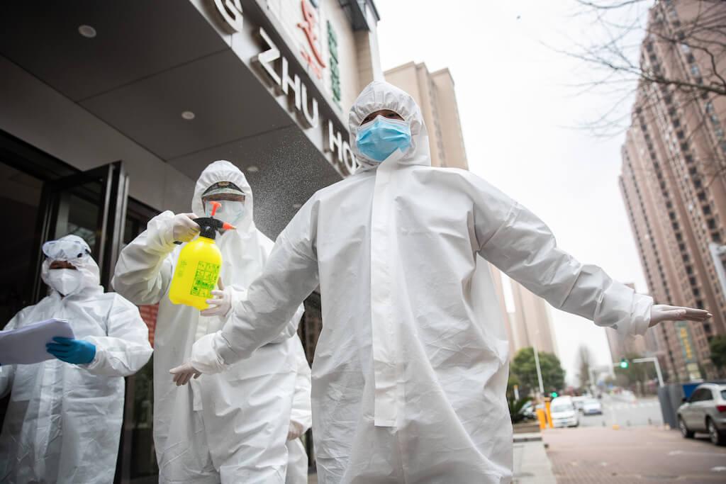 武漢一間隔離康復患者的酒店外,穿上全副保護裝備的防疫人員為彼此消毒。(圖片/法新社)