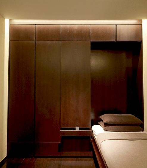 兒子的睡房,天花板只有一盞主燈,卻線條明 晰。燈槽的LED 令沉色家具變得明快。