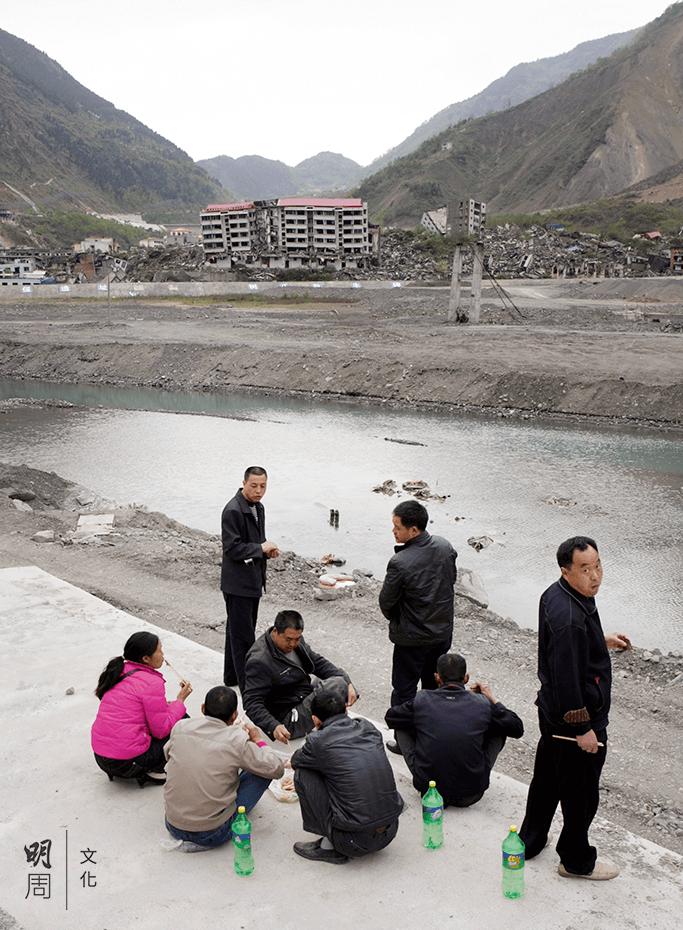 參加「地震遺址一日遊」的遊客絡繹不絕,走累了就野餐休息,四周是過萬人長眠於此的廢墟。