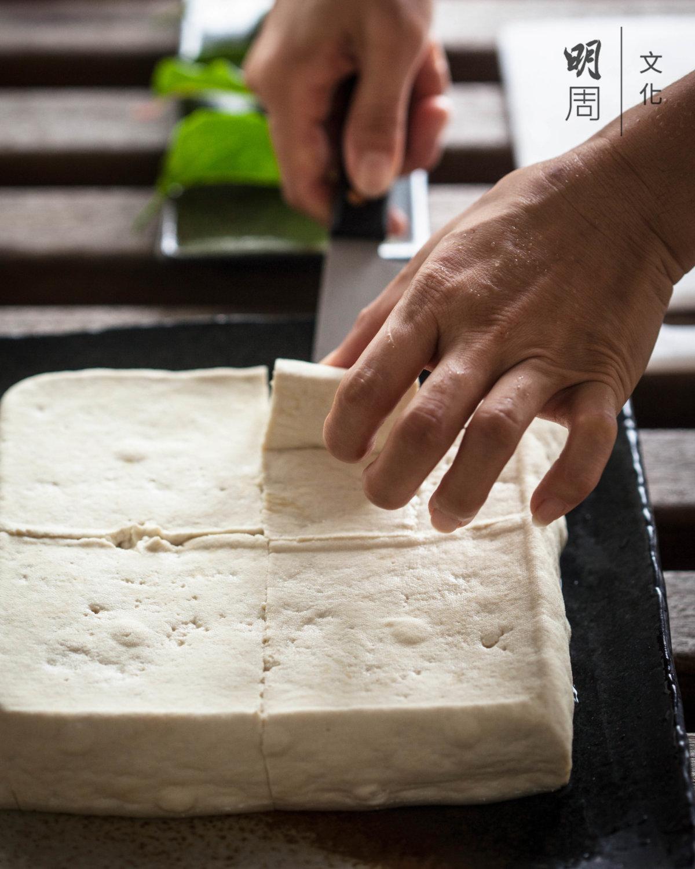 從黃豆磨成水狀,熬煮,親手榨 出豆漿,加入鹵水凝結,以及最後壓模成形。