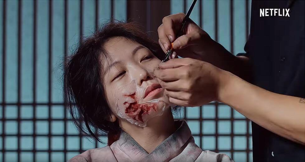 化妝師首先在面上貼上疤痕假皮。
