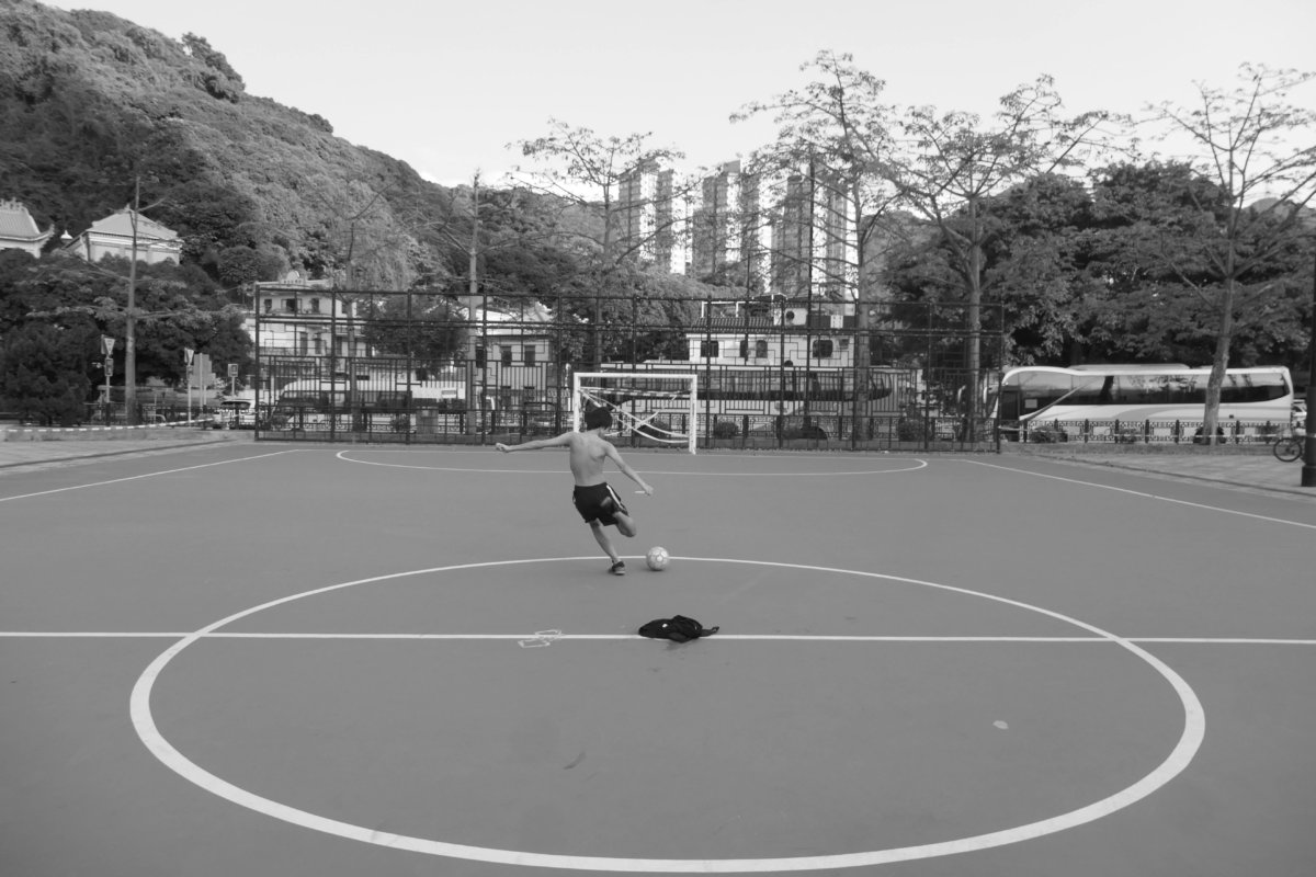 Teenager shooting at an open goal on a closed football pitch, near Che Kung Temple, Tai Wai, New Territories, 20 April 2020. (Photos: John Batten)