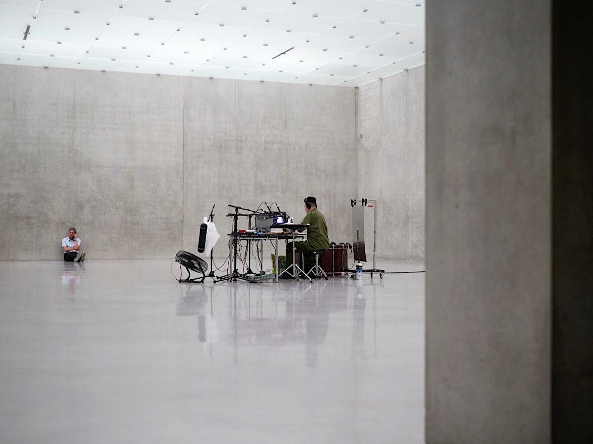 戰爭和衝突是Samson作品出經常出現的主題。聲音演出《夜曲》(2015),他以日常之物為戰爭片段現場配上爆炸聲、槍聲和雜音。圖為2018年的演出照。圖片提供:Hamburger Bahnhof及藝術家。攝影:Miro Kuzmanovic。