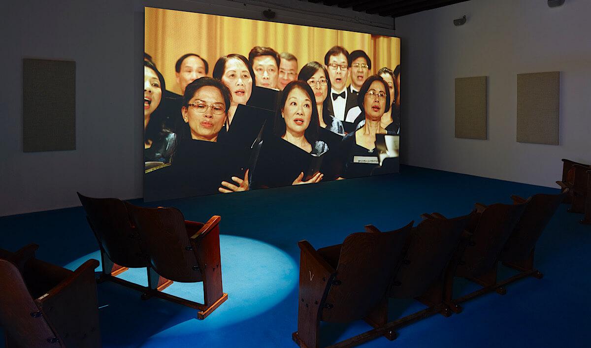 2017年的威尼斯雙年展中其中一個錄像是由香港工聯會合唱團唱出消音版的《We are the World》一曲,不同人自有不同解讀;圖片由藝術家提供。攝影:Simon Vogel