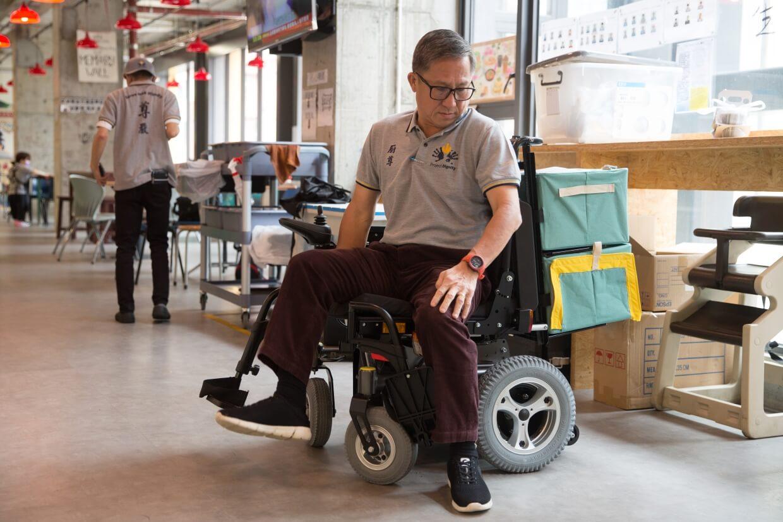 許承俊親身示範殘障員工如何轉身,再取出「車」後的外賣,送到客人手上。