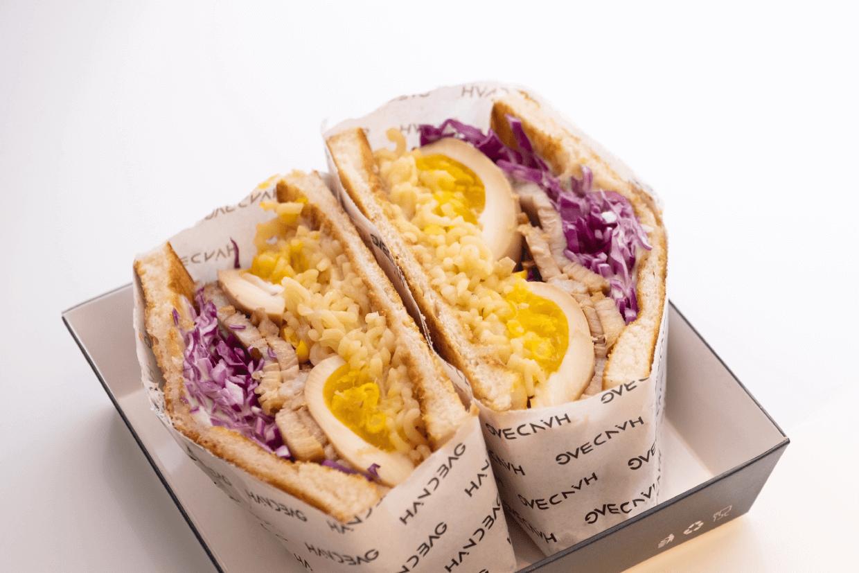 一隻大碗換成了兩片脆麵包,包覆着拉麵、味噌「湯底」、溏心蛋、叉燒、味符筍絲及粟米粒。味道疑幻似真,正是邊行邊吃的手提式「拉麵」。