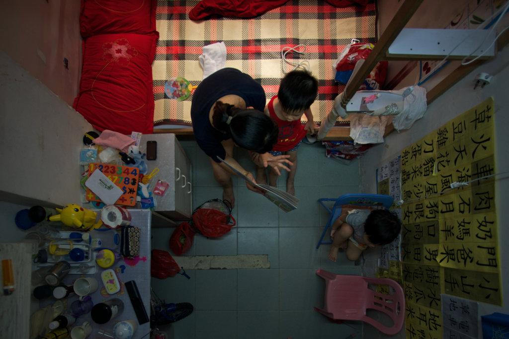 高仲明作品《「毫」宅》。在細小的劏房中,一個母親在教兩個幼兒讀書寫字