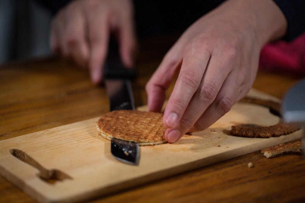 煎餅剛壓好,就要用刀俐落一片,一分為二;不急,但記得要快。