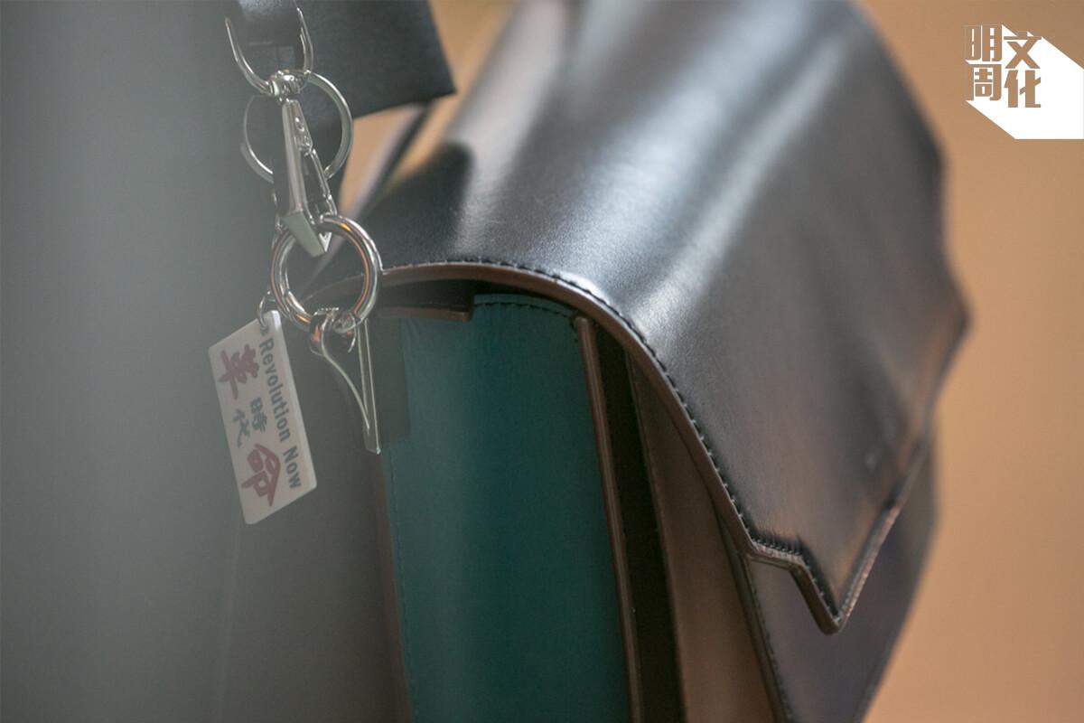 精緻的手袋,掛上小巴站牌造型的「時代革命」鎖匙扣,伴隨蔡梓蘊出入警署和法庭。