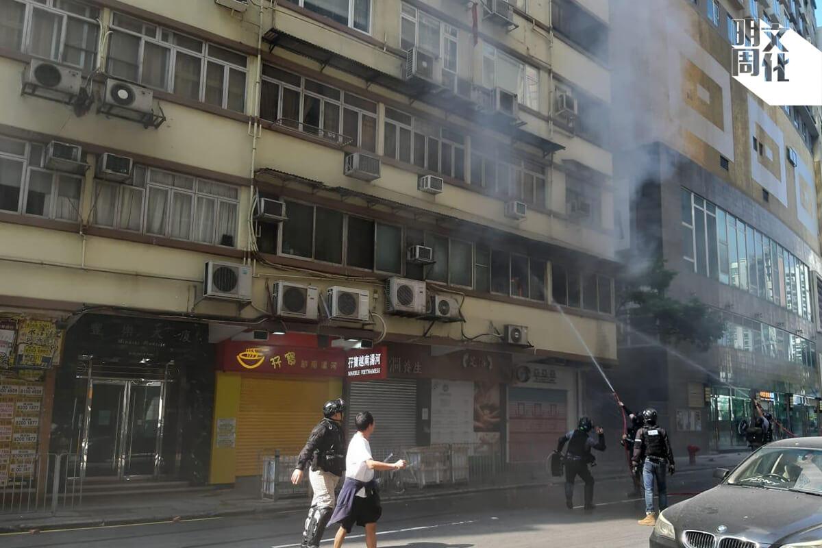 大廈旁邊的餐廳老闆,用手機拍攝在場警員行動。救火期間,有人向單位丟磚及射水。