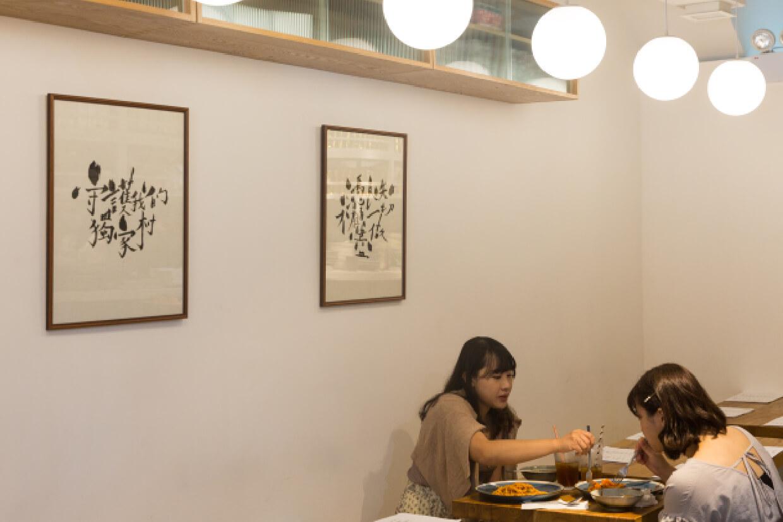 新店一畫一物都代表着店主的喜好及態度,例如餐盤內的素食料理、牆架上的黑膠唱片,以及牆上由藝術家「賣字」大手一揮的書法字畫「憑良知不顧一切盡做」。