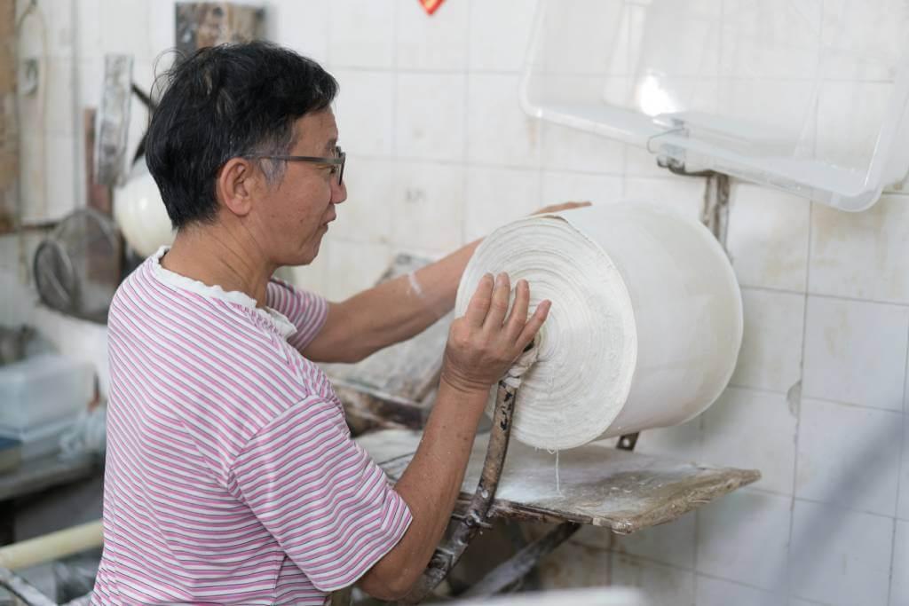 將三十多斤的麵皮抬到另一部機器壓薄,少一點氣力也不成。