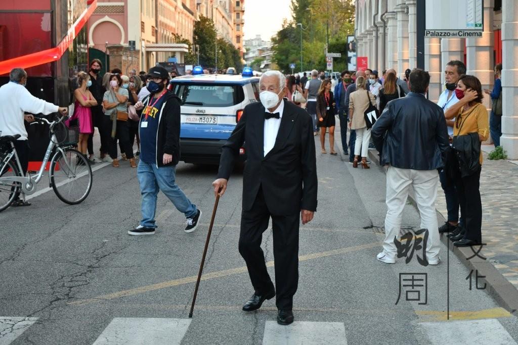 西裝筆挺的老翁走過威尼斯街道,參加影展。