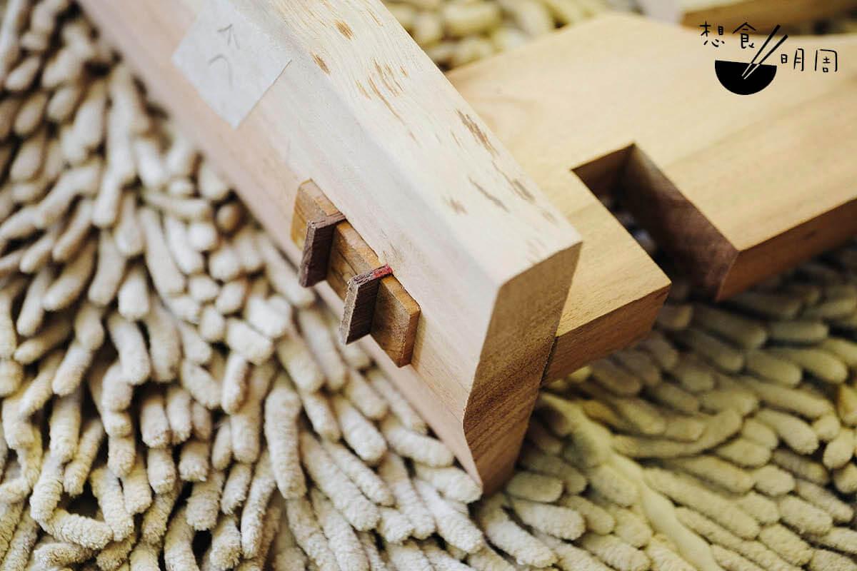 在木工的世界內,榫卯的形態及接合方式變化萬千。在拼接木腳時,家維預製了兩片小「卡片」,插入預留的隙縫中,再以木槌及膠水加固,最後再切走多餘部分,打磨後即成。