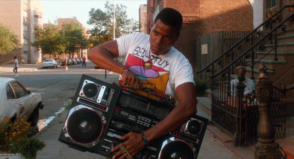 《Do the Right Thing》(1989)劇照,圖中為主角Radio Raheem(Bill Nunn飾)。他常提着其Promax J1 Super Jumbo Boombox通街跑播歌。