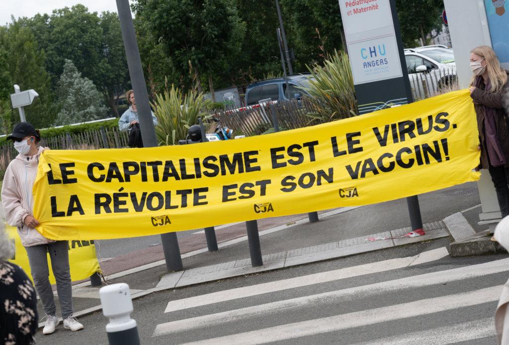 今年年中,有法國示威者在醫院門前拉起寫有「資本主義是病毒,革命是疫苗」字樣的橫額。(圖片:法新社)