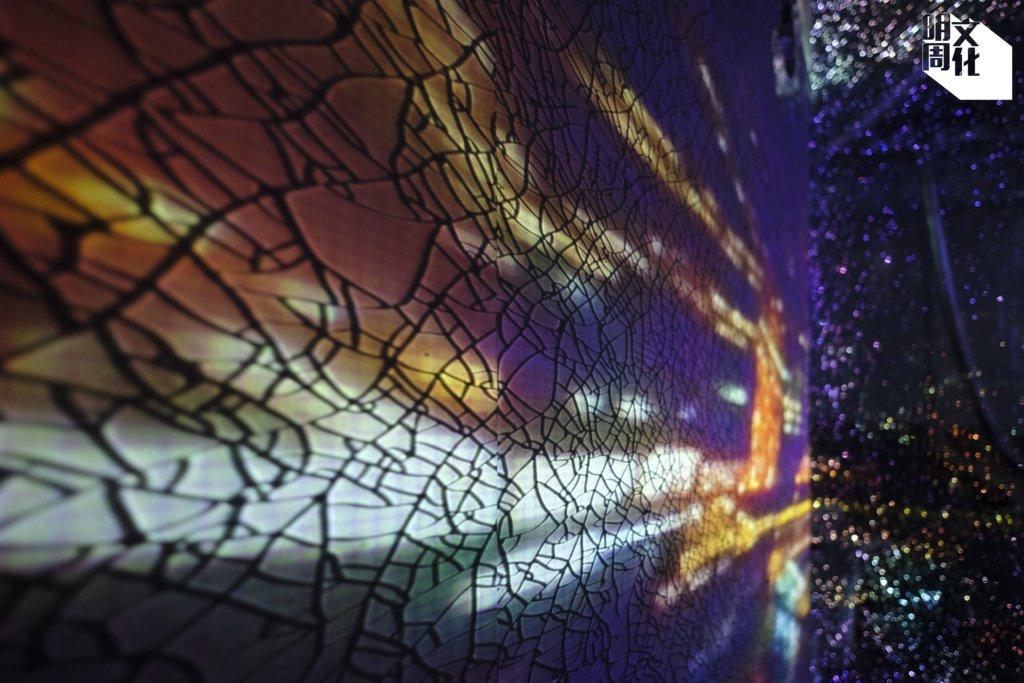《迷惑的光》將「幻彩詠香江」錄像投影在破裂的玻璃上,是對城市繁華表象的嘲諷。
