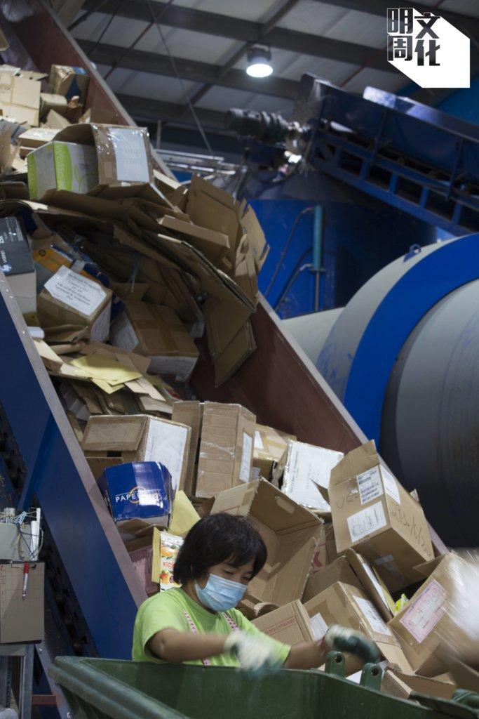 廠房內,工人不停將收集得到的廢料放上運輸帶。