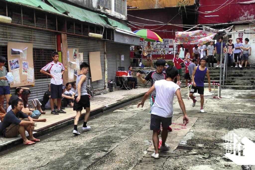 仁信里空地上,放置膠水管砌成小龍門,成為「人民足球」比賽場地,運動員和街坊以汗水和笑聲,向老社區道別。(圖片由盧樂謙提供)