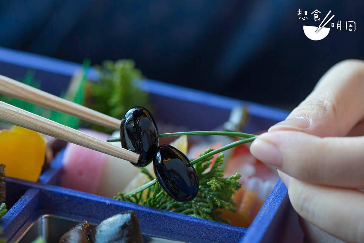 選用京都黑豆,先用梳打水浸泡一天至軟,然後蒸煮一天。用凍水過冷河後,即泡在糖水四天,最後加豉油及鹽調味。這樣子吃來才夠軟糯香甜。