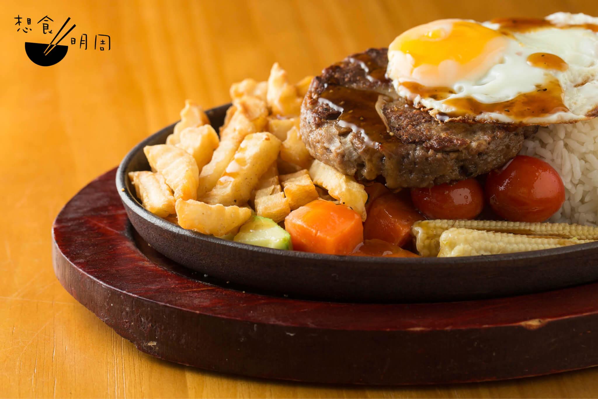 鐵板IMPOSSIBLE漢堡扒煎蛋飯配黑椒汁 // 現成素漢堡經廚師再次調製,並搓 入洋葱粒、麵包糠,製成漢堡扒,連同煎薯菜、煎蛋一同上碟。上桌時依然「滋滋」作響,正是港式快餐不能缺少的滋味。($88)