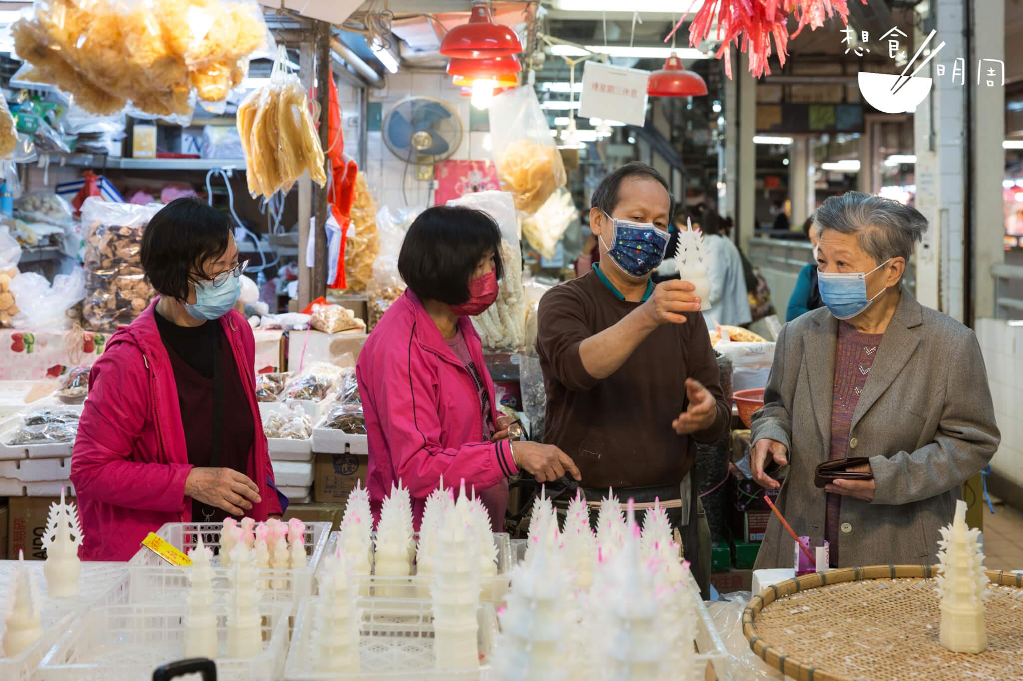 忠記雜貨店老闆鍾松弟一邊跟街坊介紹糖塔,一邊為他們挑選最好的。
