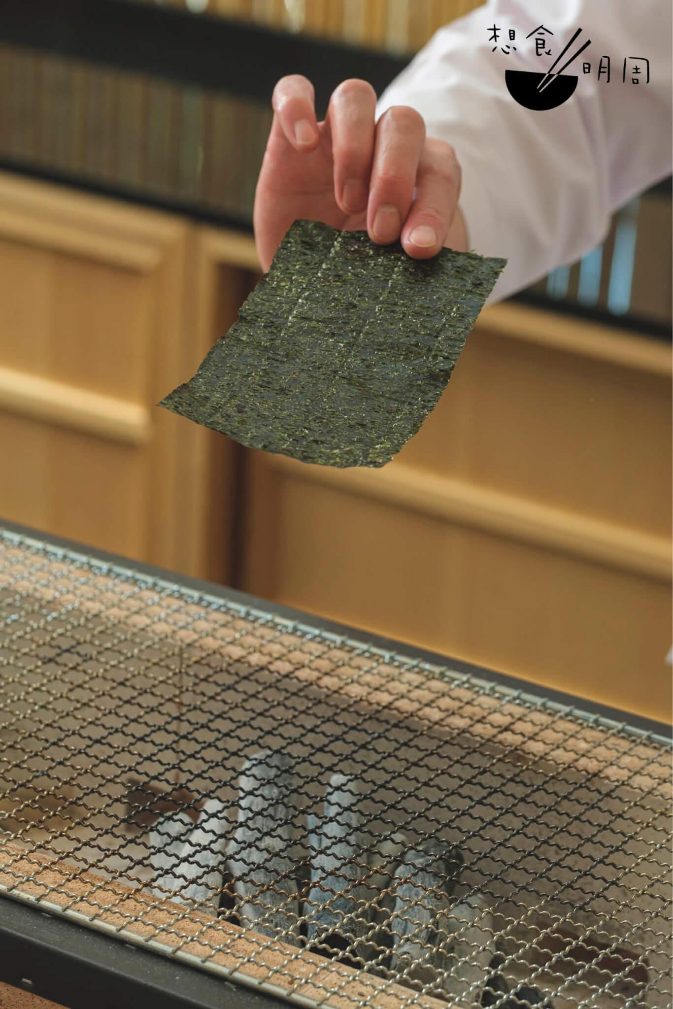 把紫菜來回在炭上輕拂,以求烘得一片香脆,再包覆吞拿魚蓉製成小卷,遞向席前客人手上。