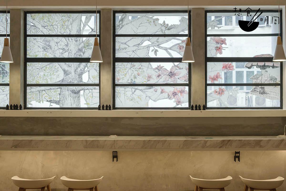 店內的大玻璃窗上,是香港版畫師林敬庭的拼貼作品「離離樹花」,期望重現白田壩街木棉樹因大廈的阻擋而缺少了的一半枝葉。