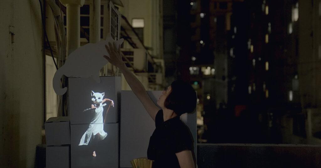 梅卓燕在舊式騎樓尋貓,其愛貓「盲豬」早年去世,而紙板道具為過往演出所用。