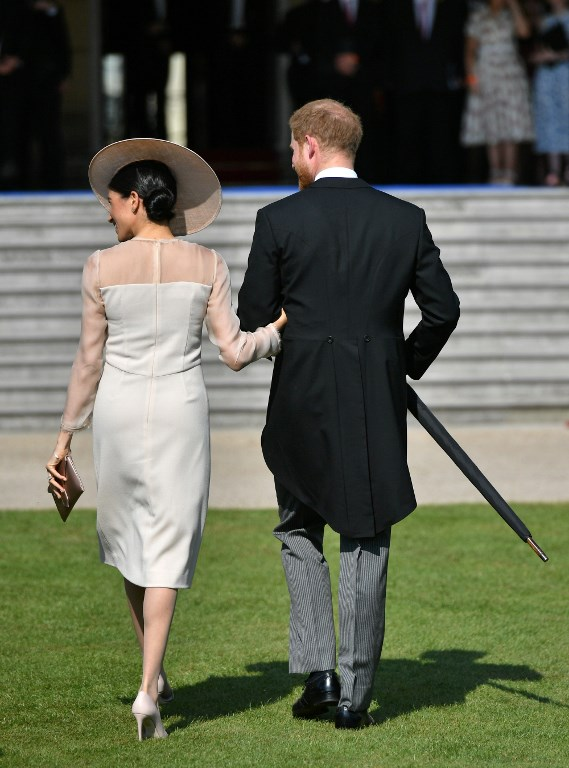 Britain's Prince Harry, Duke of Sussex (R), and his new wife, Britain's Meghan, Duchess of Sussex, attend the Prince of Wales's 70th Birthday Garden Party at Buckingham Palace in London on May 22, 2018. The Prince of Wales and The Duchess of Cornwall hosted a Garden Party to celebrate the work of The Prince's Charities in the year of Prince Charles's 70th Birthday. / AFP PHOTO / POOL / Dominic Lipinski