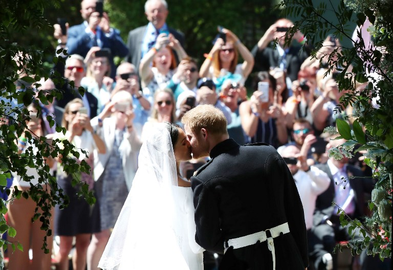 Britain's Prince Harry, Duke of Sussex kisses his wife Meghan, Duchess of Sussex as they leave from the West Door of St George's Chapel, Windsor Castle, in Windsor, on May 19, 2018 after their wedding ceremony. / AFP PHOTO / POOL / Danny Lawson