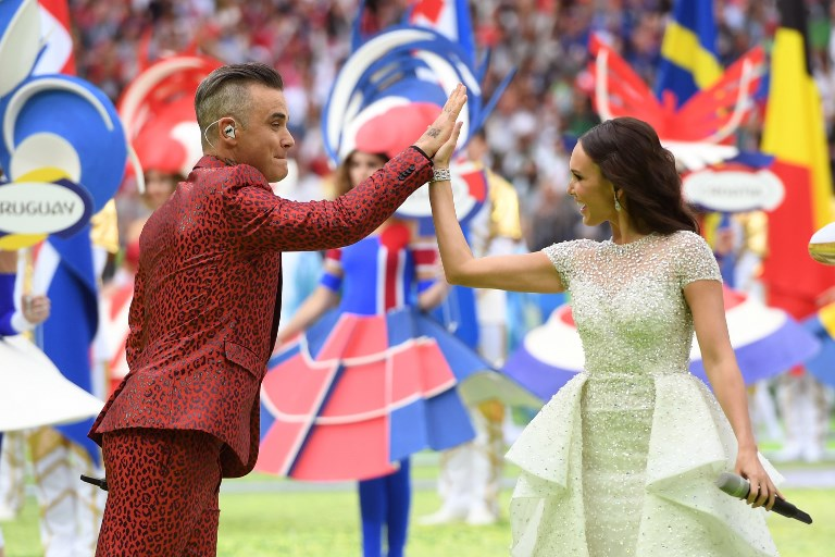English musician Robbie Williams (L) and Russian soprano Aida Garifullina perform during the Russia World Cup opening ceremony before the tournament's first match between Russia and Saudi Arabia on June 14, 2018 at Moscow's Luzhniki Stadium. / AFP PHOTO / Patrik STOLLARZ