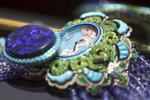 18K白金及鈦金神秘腕錶,鑲嵌一枚72卡歐泊、雕刻翡翠、綠松石、縞瑪瑙、梨形及明亮式切割鑽石、明亮式切割祖母綠及明亮式切割丹泉石。精緻的錶盤鑲嵌粉紅色珍珠貝母及玉髓,呈現青空中的晨光,絢麗奪目。錶鏈由合共235卡的丹泉石圓珠組成。