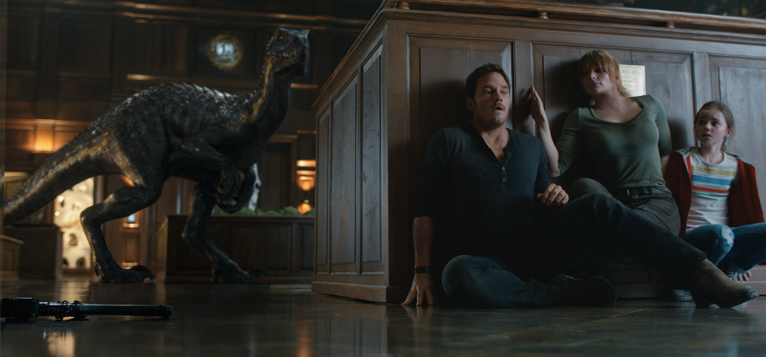 "The Indoraptor stalks its prey—(L to R) Owen (CHRIS PRATT), Claire (BRYCE DALLAS HOWARD) and Maisie (ISABELLA SERMON) in ""Jurassic World: Fallen Kingdom."" When the island's dormant volcano begins roaring to life, Owen and Claire (Bryce Dallas Howard) mount a campaign to rescue the remaining dinosaurs from this extinction-level event. Welcome to ""Jurassic World: Fallen Kingdom."""
