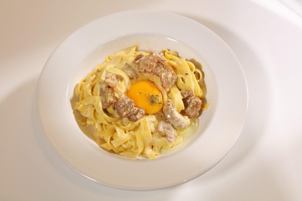 闊條麵以忌廉汁配自家醃肉來炒,加上日本生蛋,口感香濃。