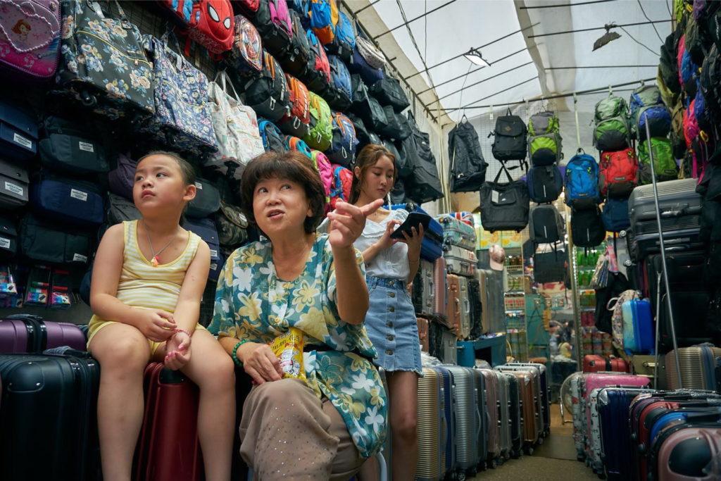 朱咪咪在戲中飾演賣行李箱及背包的檔販,看她的表情已充滿喜感。