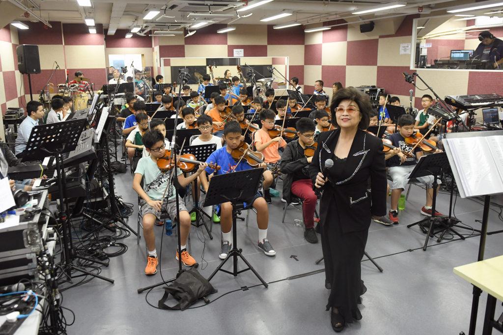 徐小鳳與數十位小學生管弦樂手綵排,練習《漫漫長路》、《風的季節》等歌曲。