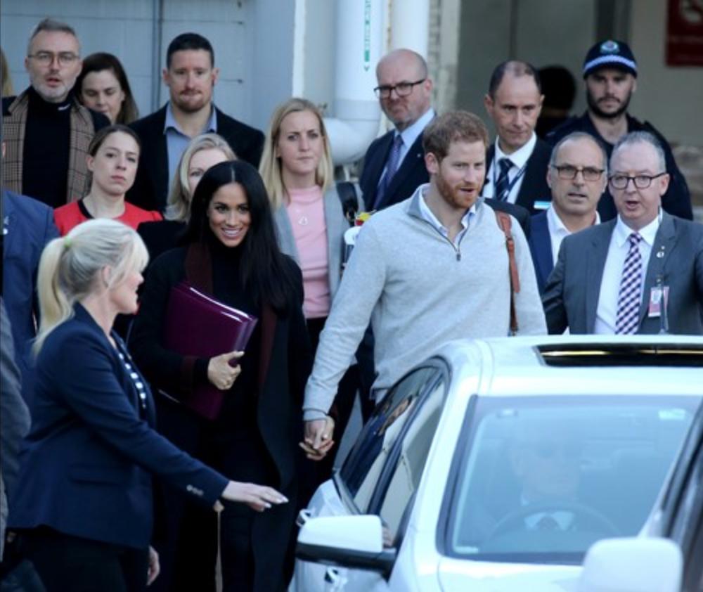 梅根今日與哈里出訪澳洲時,全程用文件夾遮肚,令懷孕傳聞甚囂塵上。