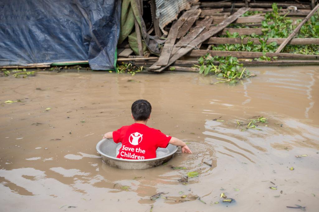 在水上村莊,村民以鐵盆作渡河工具,Cathy的子女們也試坐。