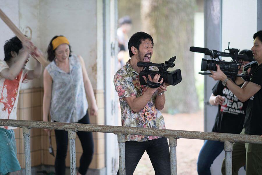 濱津隆之飾演的日暮隆之眼見喪屍來襲,仍強迫眾人冒死拍攝,非常癲狂。