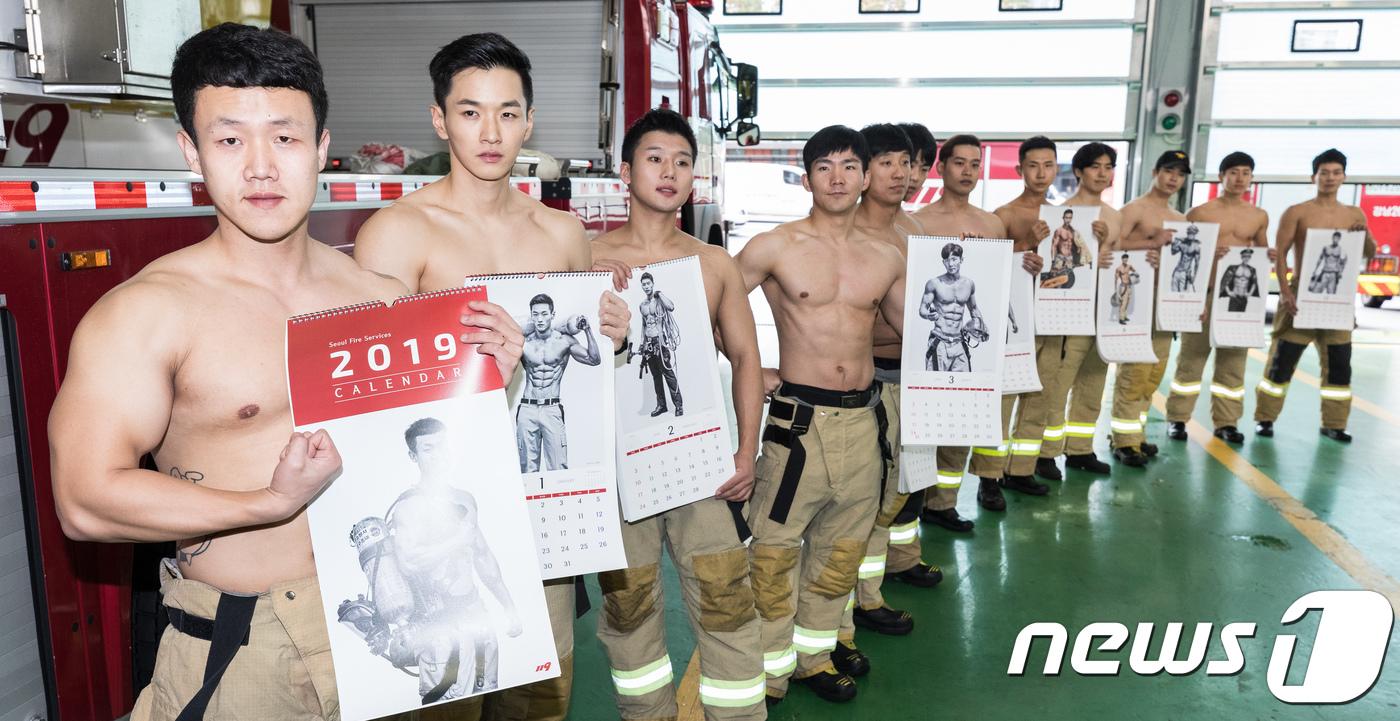 一班「猛男消防員」拿着自己剛出爐的寫真月曆合照紀念