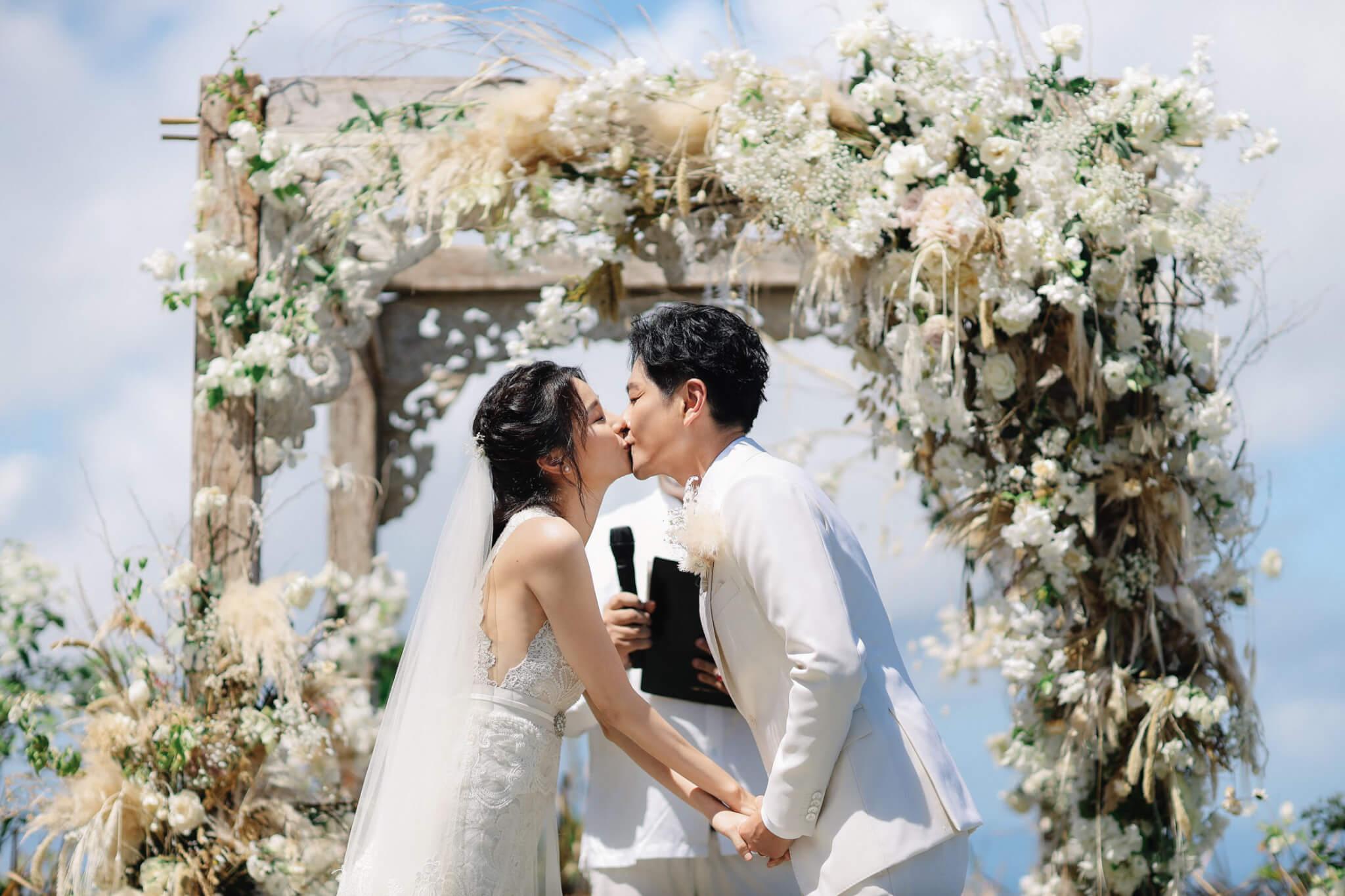 一對新人在彩虹下交換戒子、擁吻,浪漫又溫馨。