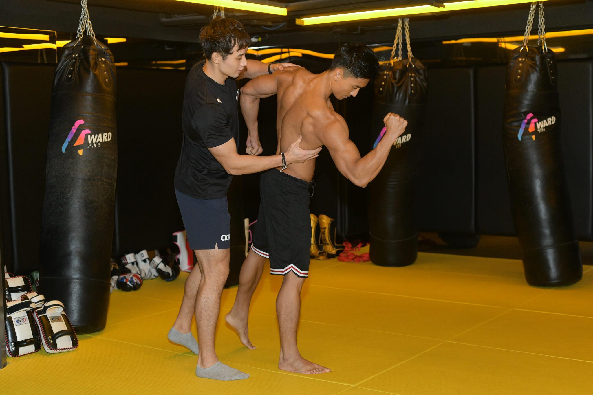教練親自教導站在台上的甫士,要他盡量展現肌肉美。