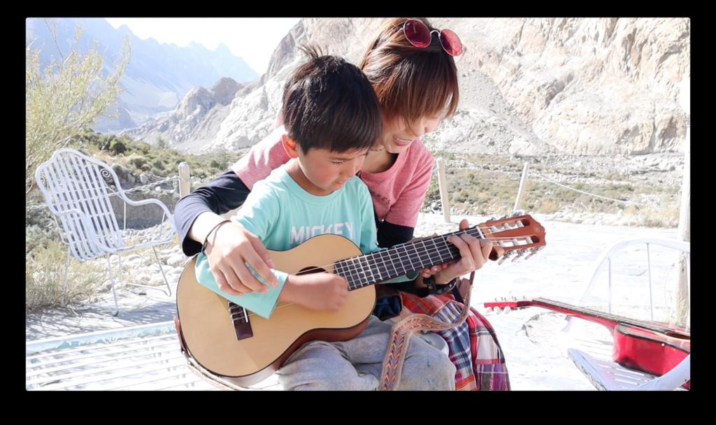 慧敏抱着路過的小孩一起合奏一曲,她負責按弦,小孩負責彈奏。